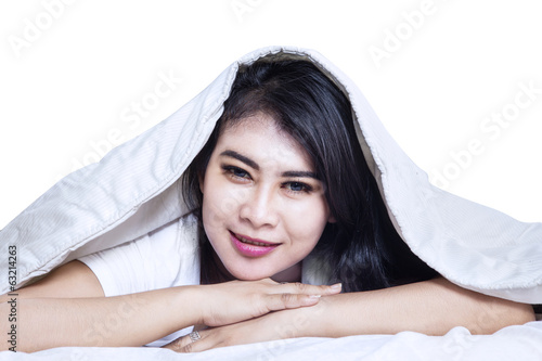 Happy asian woman under the blanket