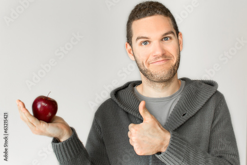 Young man holding an apple and thumb up