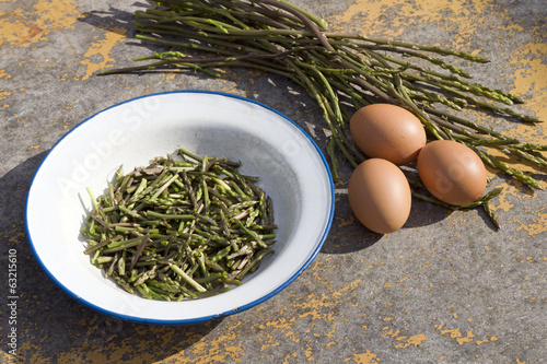 Plate with chopped wild asparagus and three eggs on table