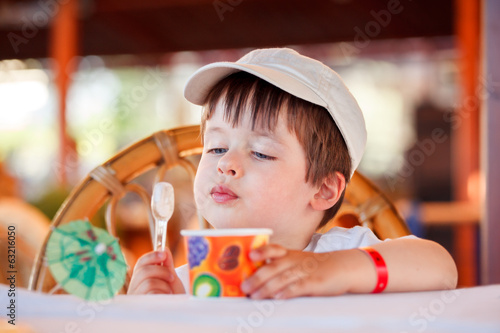 Cute little boy eating ice cream at indoor cafe