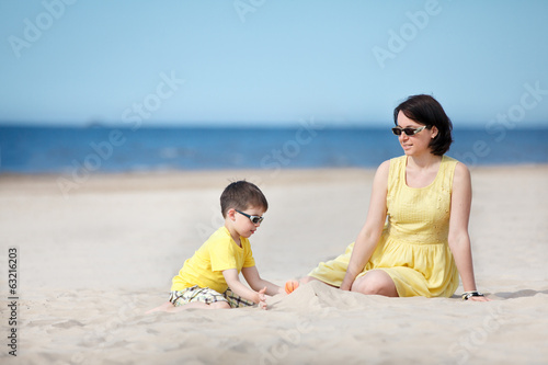 Young mother and son playing on sand beach