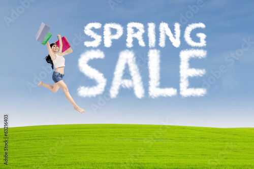 Shopaholic jumps with spring sale sign