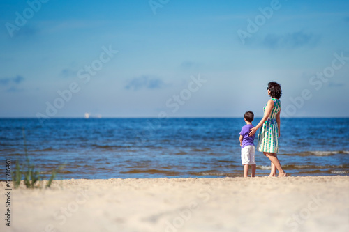 Back view of mother and her son at summer beach
