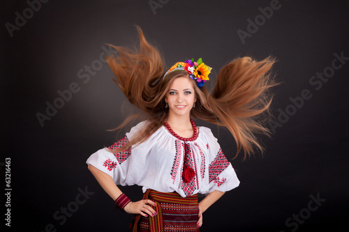 Portrait of a beautiful girl with flying brown hair. Woman wears