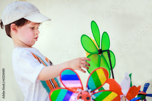 Cute little boy with windmill toys outdoors