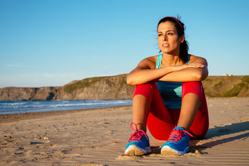 Relaxed fitness woman resting at beach