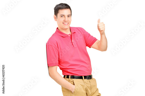 Smiling man leaning against wall and giving a thumb up