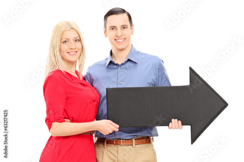 Young couple holding a big black arrow