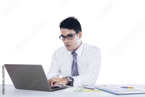 Young businessman typing on laptop computer
