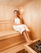slim woman in towel sitting on bench at sauna next to oven