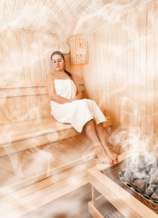 Sexy woman in steamed finnish sauna sitting with closed eyes