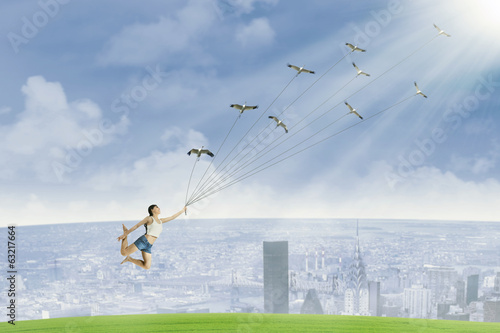 Young woman is flying by holding birds