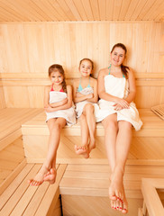 Photo of happy mother with two daughter relaxing at steam bath