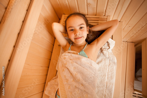 Closeup portrait of little girl lying at sauna