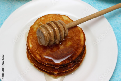 Pancakes and honey on white dishware