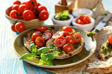 Bruschetta with fresh cherry tomatoes and aromatic herb pesto
