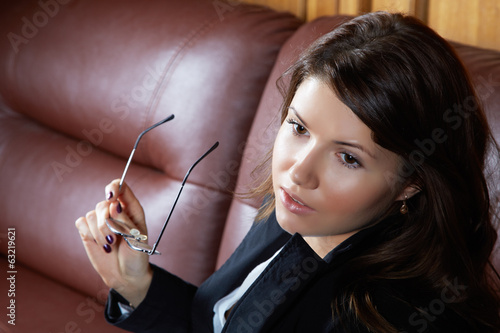 The girl in a suit sits on  leather sofa
