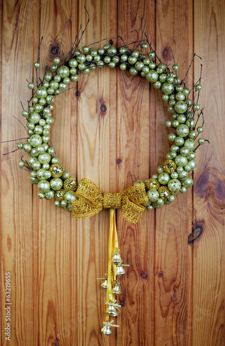 The wedding wreath hangs on a wooden wall