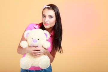 Childish woman infantile girl in pink hugging teddy bear