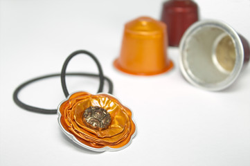 DIY jewelry made with espresso capsules over white background
