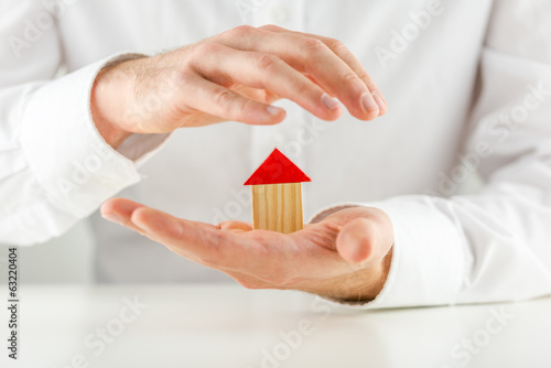 Man protecting a model house in his hands