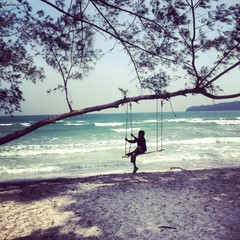 child on home made swing under tree on beack in cambodia