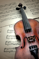 Old scratched violin on music sheet. Vintage style.