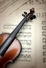 Detail of old scratched violin on sheet music. Vintage style.