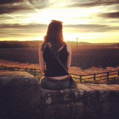 girl enjoying sunset sitting on wall in yorkshire