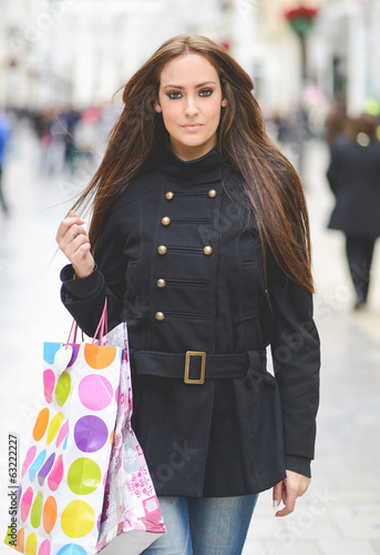 Attractive young woman with shopping bags in a commercial street