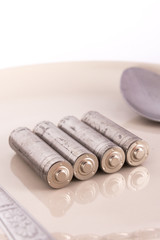 isolated of old AA battery in food dish is energy consumption co