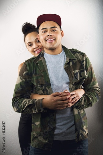 Young couple in love together on grey background