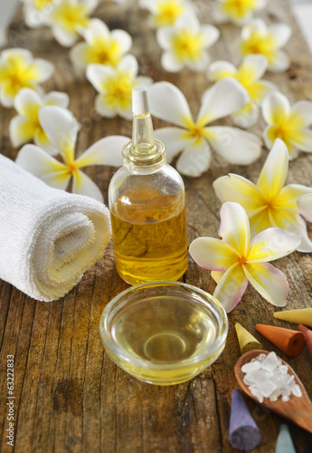 frangipani ,towel,oil, salt in spoon with wood in background