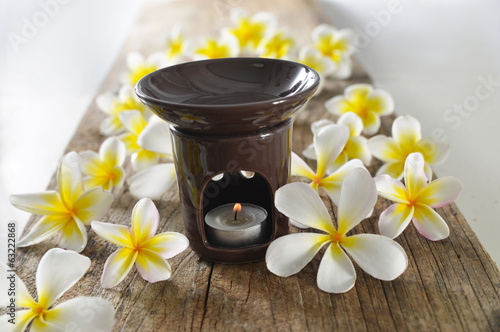 white and yellow frangipani with candle on old wood