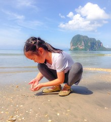 a girl collecting sea shell on the beach