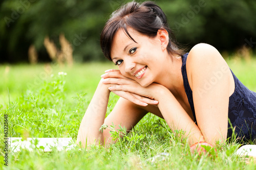 Young woman lying on grass with book