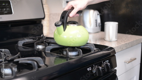 Person pours hot watter, focus on kettle