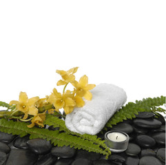 towel with green fern and yellow orchid ,candle on pebbles