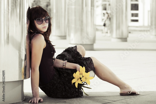 Sad young woman with a flowers sitting on the sidewalk