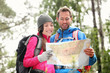 Hiking couple looking at map hiking in forest