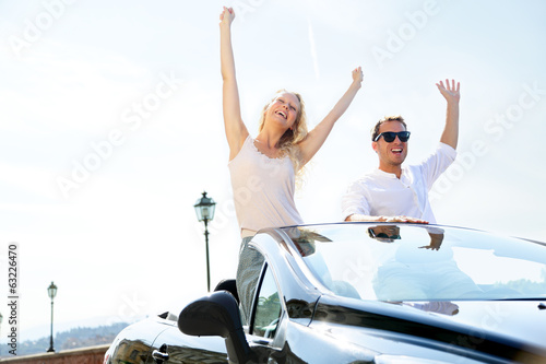 Happy people in car driving on road trip