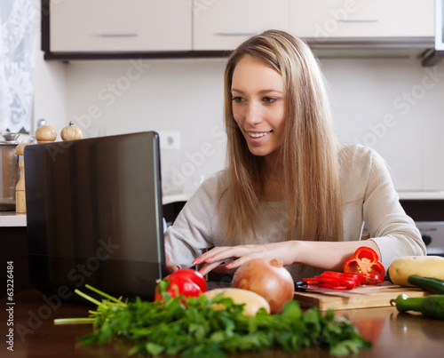 Smiling woman  with notebook in  kitchen