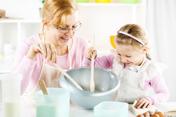 Grandmother and granddaughter in a kitchen.