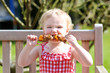 Funny toddler girl eating bbq meat outdoors in the garden - 63227610
