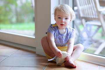 Little girl puts on her shoe sitting on the floor next window