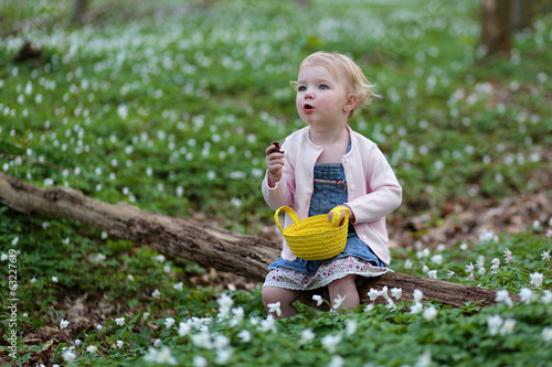 Cute toddler girl enjoying eggs hunting in forest on Easter day