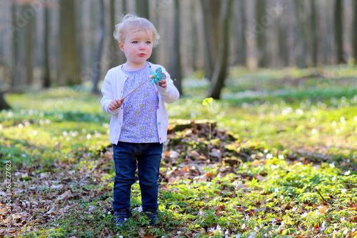 Cute toddler girl playing in the forest on sunny spring day