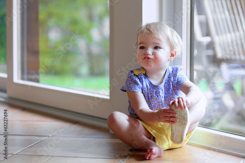 Little girl puts on her shoe sitting on the floor next window