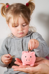 savings concept, child holding coin with piggy bank