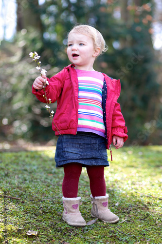 Happy toddler girl in casual clothes playing in spring park